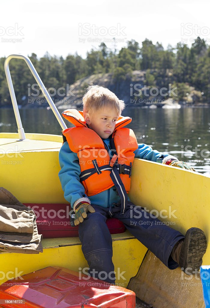 Small bored boy with life jacket in yellow boat royalty-free stock photo