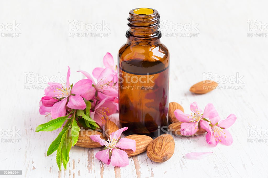 small bottle of almond oil, almonds and flowers stock photo