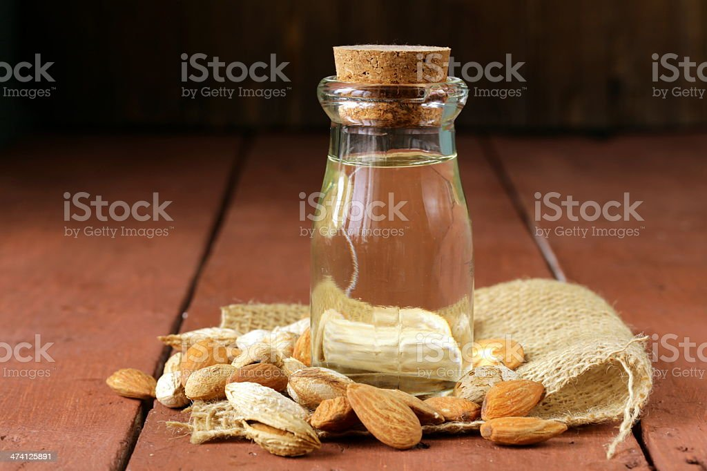 A small bottle of almond oil, with nuts surrounding it stock photo