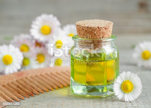 istock Small bottle of cosmetic chamomile oil and wooden haircomb 533351050