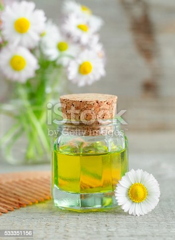 istock Small bottle of cosmetic chamomile oil and wooden haircomb 533351156