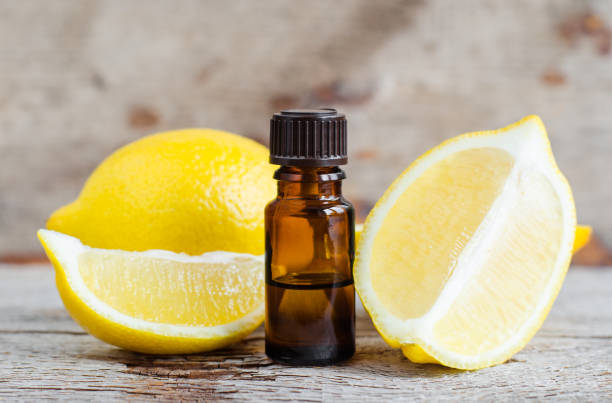 small bottle of essential lemon oil on the old wooden background. aromatherapy, spa and herbal medicine ingredients. copy space. - oli, aromi e spezie foto e immagini stock