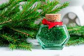 Small bottle of green bath salt and fir branches.