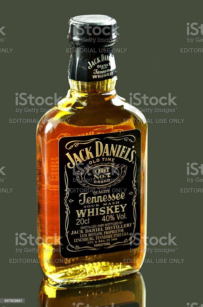 Pequeña botella de whisky Jack Daniels aislado sobre fondo oscuro - foto de stock