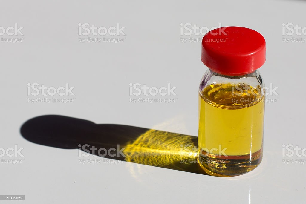 Small bottle of yellow oil with the red cap stock photo