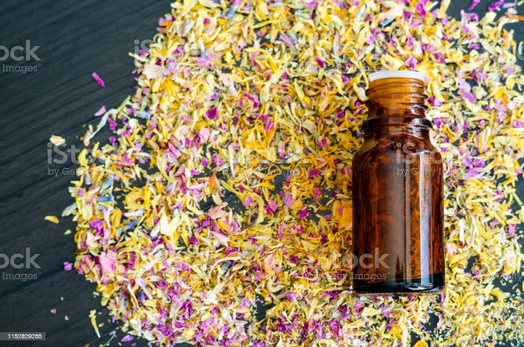 Small Bottle With Essential Oil And Dry Herbs And Flowers