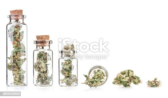 Small bottle with medical marijuana buds, closeup, isolated on white background. Therapeutic and medical cannabis
