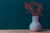 Small Bouquet of Red Flowers in Vintage Vase on Wood Table Blue Navy Wall Background. Styled Stock Image Mockup for Text Artwork Quotes Lettering Website Banner Template. Easter Mother's Day