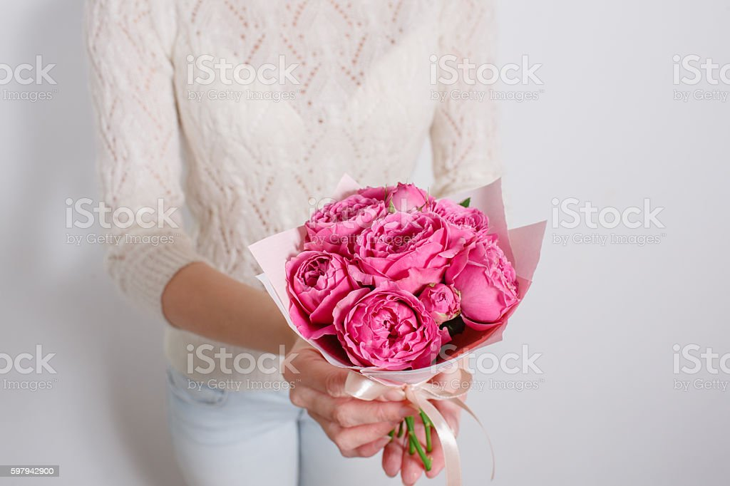 small bouquet of roses and peonies in hands girl Florist foto royalty-free