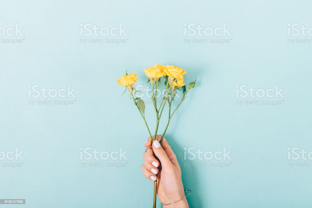 Small bouquet of yellow roses in a female hand стоковое фото