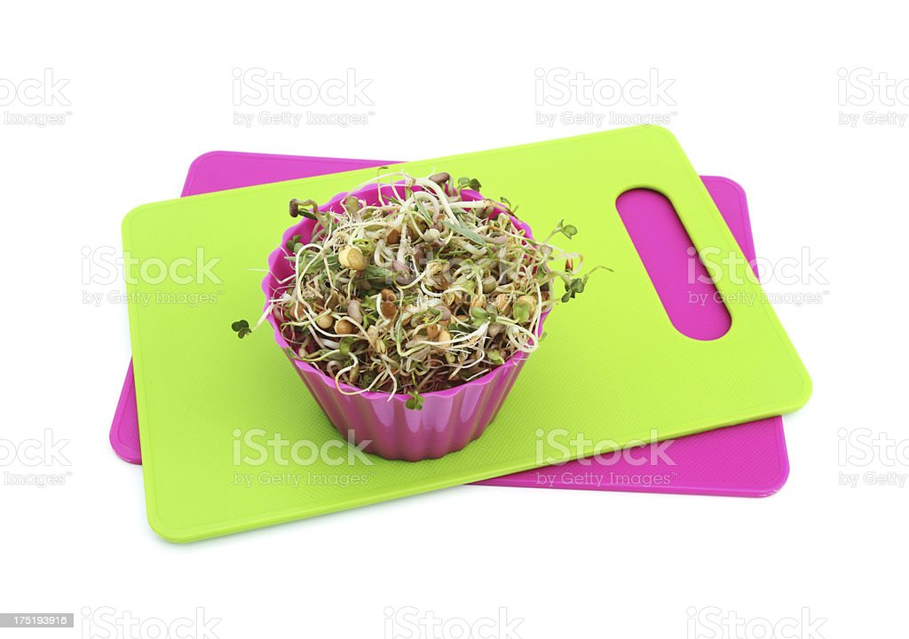 Small bowl of fresh sprouts on green cutting board stock photo