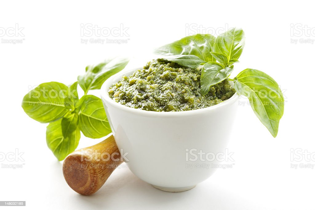 Small bowl of green pesto next to leaves stock photo