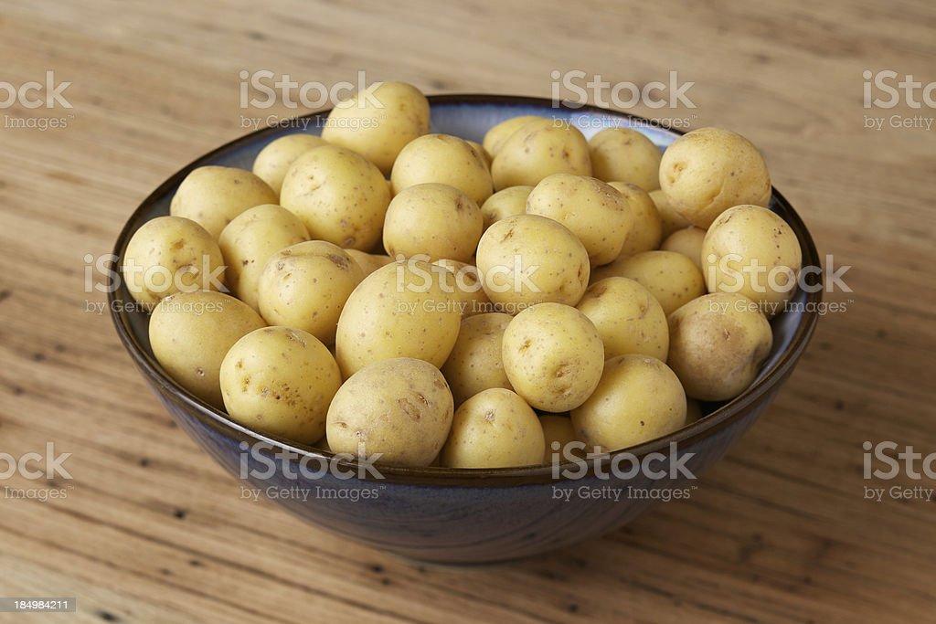 Small bowl of organic honey gold potatoes stock photo