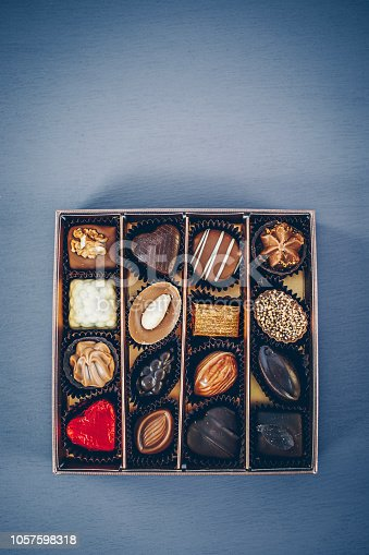 183269671istockphoto Small box of chocolate pralines and truffles assorted. Blue toned background, directly above. 1057598318