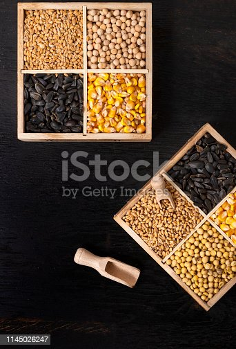 Small box with various grains and cereals on wooden table, top view, copy space