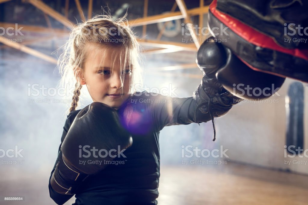 Small boxer exercising punches on a sports training in a gym. stock photo