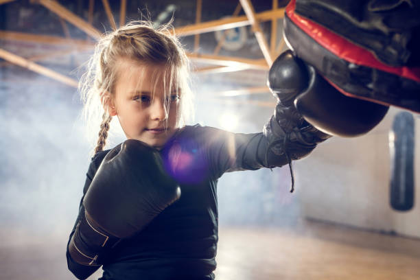 Small boxer exercising punches on a sports training in a gym. Little girl having a boxing training in a health club. self defense stock pictures, royalty-free photos & images