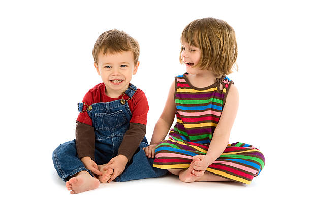 Small boy and girl sitting together smiling on white stock photo