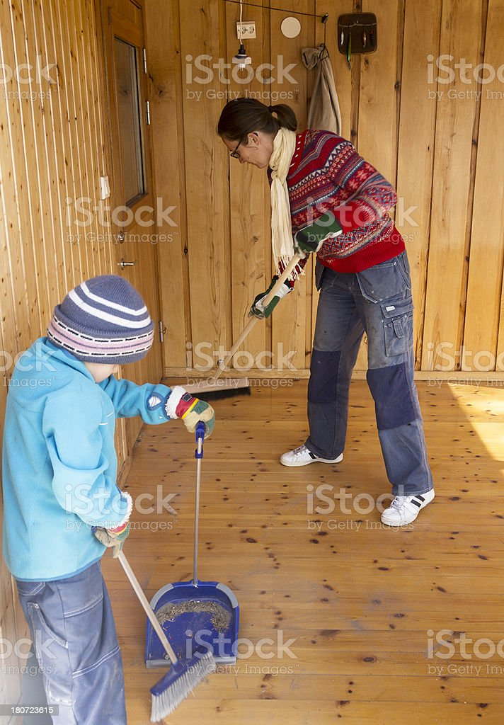 Small boy and his mother spring cleaning, sweeping wooden floor. royalty-free stock photo