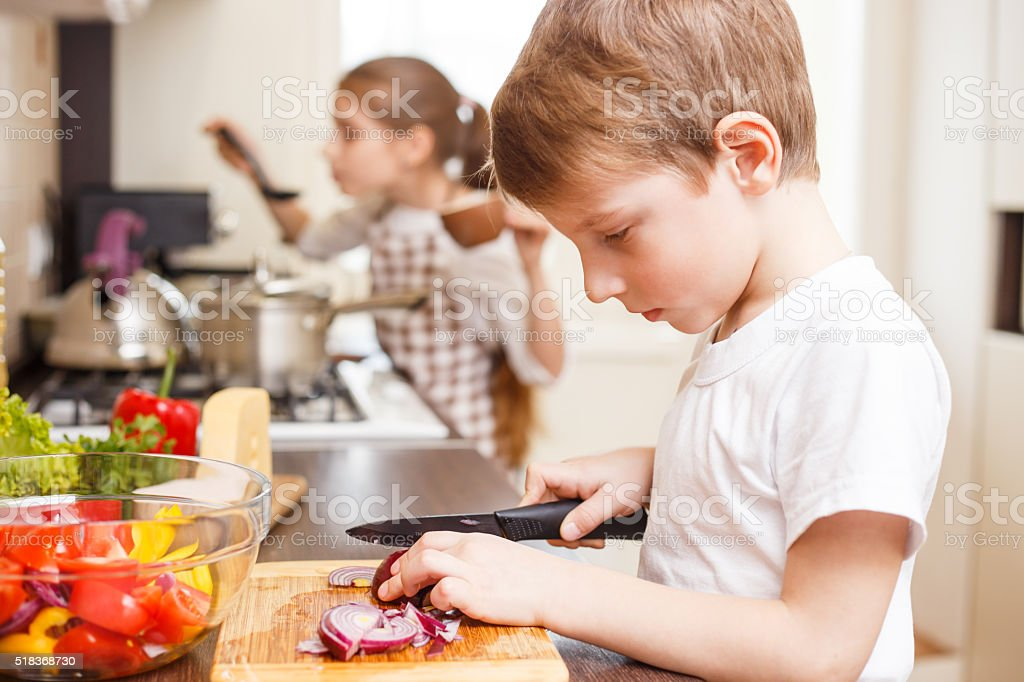 Piccolo ragazzo e sua sorella cottura in cucina - foto stock
