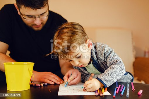 926151996istockphoto Small boy and his uncle or father sitting by the table at home playing with crayons color pencils drawing and learning family activities having fun 1187994724