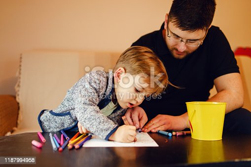 926151996istockphoto Small boy and his uncle or father sitting by the table at home playing with crayons color pencils drawing and learning family activities having fun 1187994958