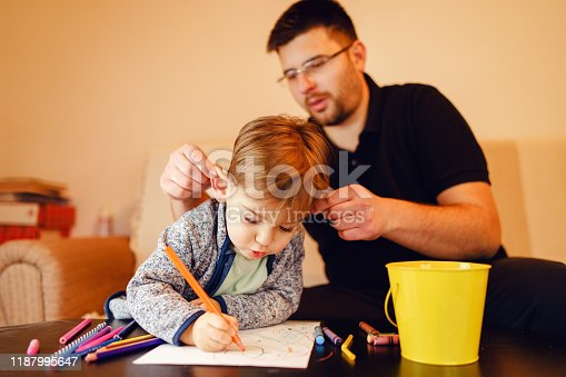 926151996istockphoto Small boy and his uncle or father sitting by the table at home playing with crayons color pencils drawing and learning family activities having fun 1187995647