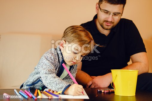 926151996istockphoto Small boy and his uncle or father sitting by the table at home playing with crayons color pencils drawing and learning family activities having fun 1187995858