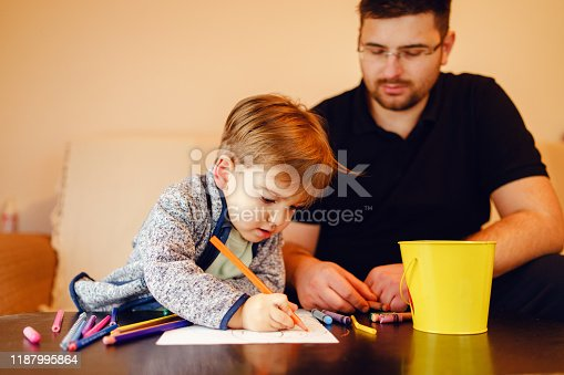 926151996istockphoto Small boy and his uncle or father sitting by the table at home playing with crayons color pencils drawing and learning family activities having fun 1187995864