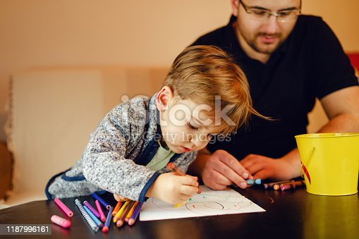 926151996istockphoto Small boy and his uncle or father sitting by the table at home playing with crayons color pencils drawing and learning family activities having fun 1187996161