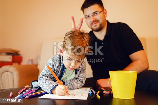 926151996istockphoto Small boy and his uncle or father sitting by the table at home playing with crayons color pencils drawing and learning family activities having fun 1187996162