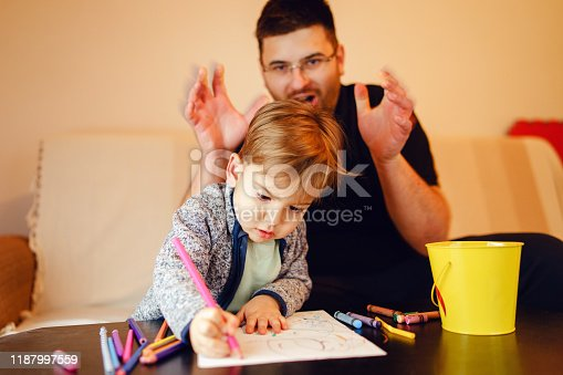926151996istockphoto Small boy and his uncle or father sitting by the table at home playing with crayons color pencils drawing and learning family activities having fun 1187997559