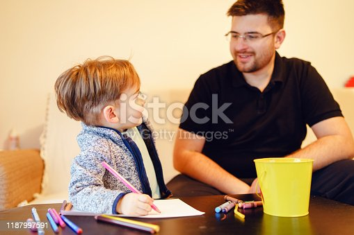 926151996istockphoto Small boy and his uncle or father sitting by the table at home playing with crayons color pencils drawing and learning family activities having fun 1187997591