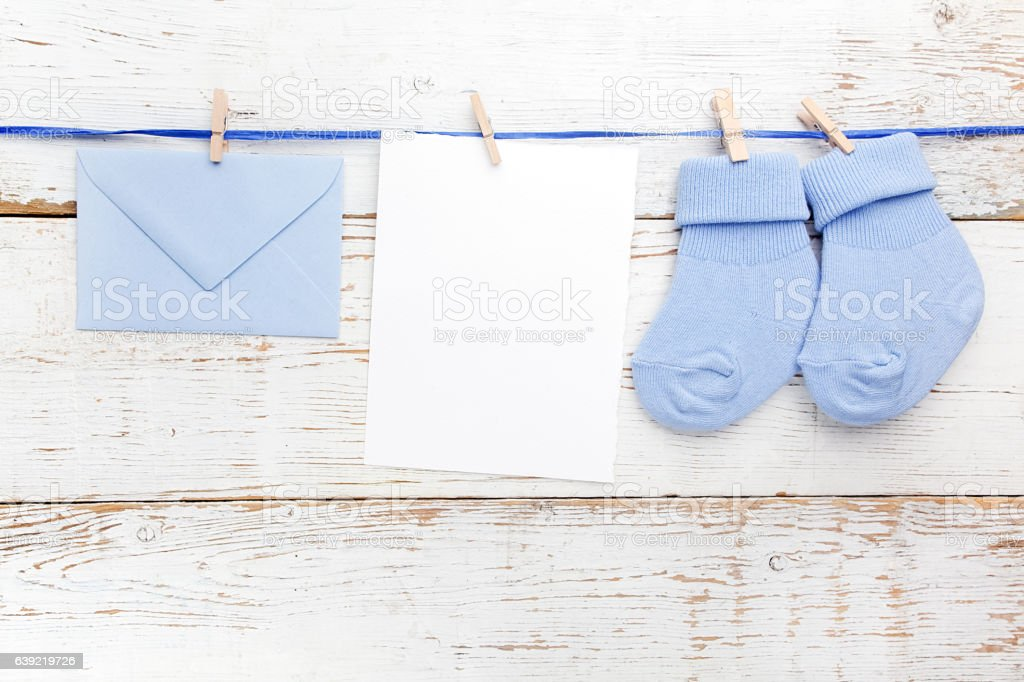 Small boy blue socks, blank card and evelop on white stock photo