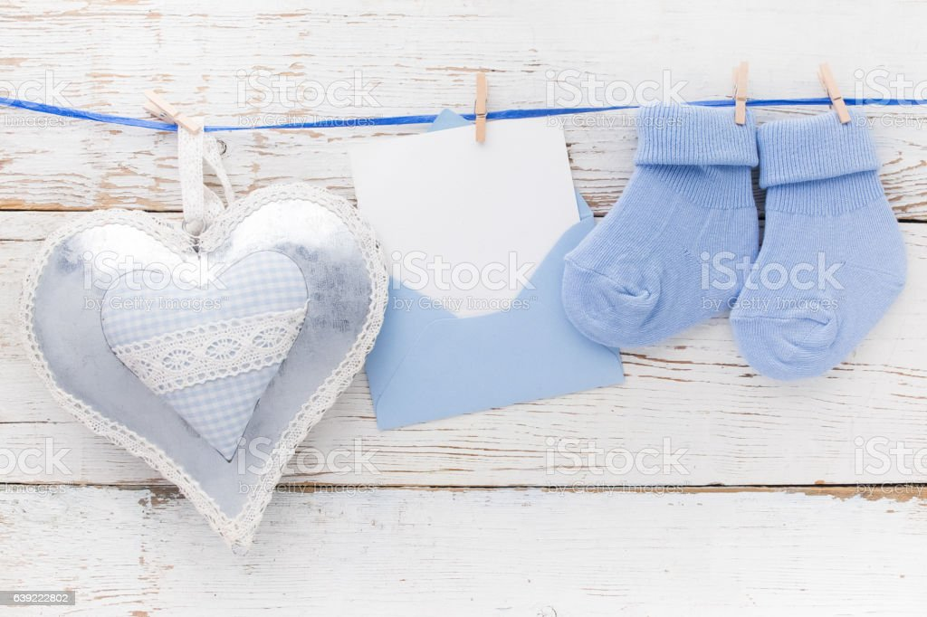 Small boy blue socks, blank card in evelop and heart stock photo