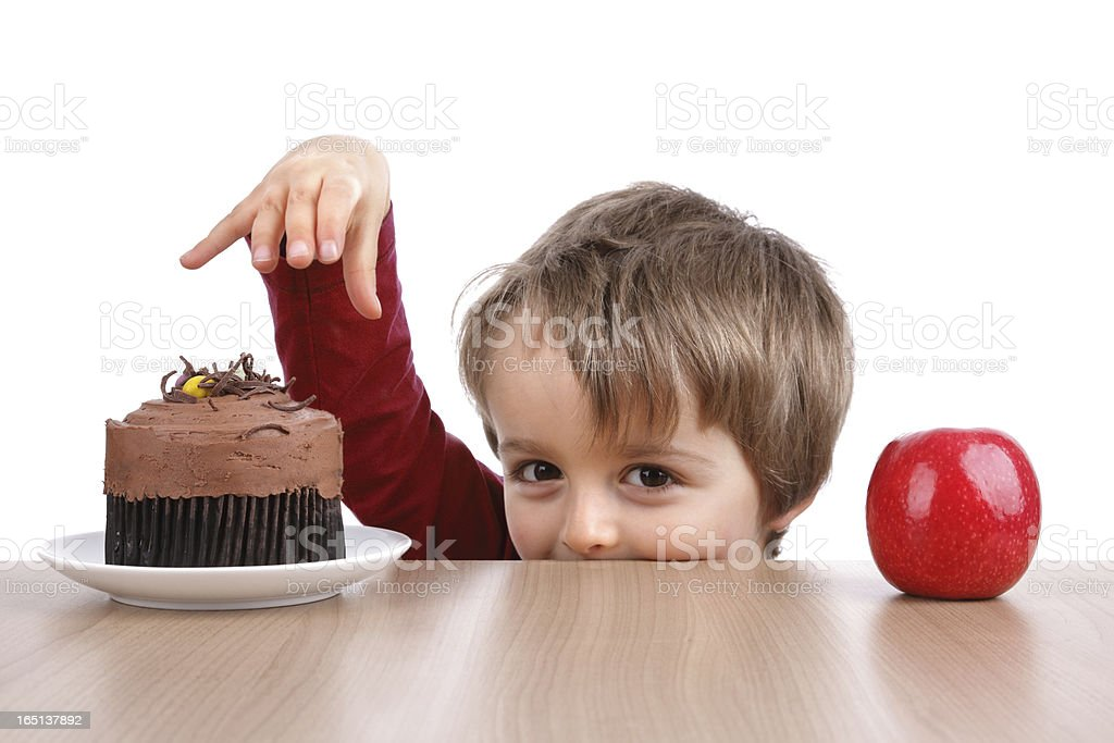 Small boy choosing to eat cake instead of an apple  stock photo