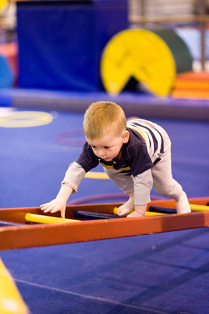 """Small Boy Climbing Ladder on Obstacle Course """"Young toddler boy concentrates as he climbs a ladder on an obstacle course during a gymnastics class. Shallow DOF focus on eyes, challenging shot made possible only with modern high end DSLR sports camera and fast pro lens."""" obstacle course stock pictures, royalty-free photos & images"""