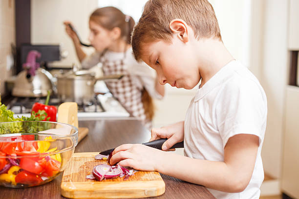 Small boy cooking together with his sister Small boy cooking together with his sister. Cute boy cutting onion for salad in the kitchen. Family cooking background sergionicr stock pictures, royalty-free photos & images