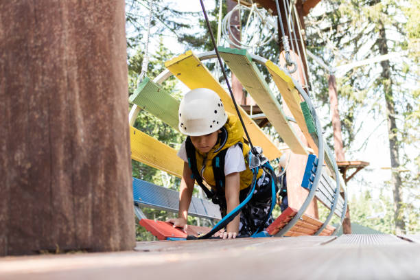 Small boy crawling through obstacles during canopy tour in nature.