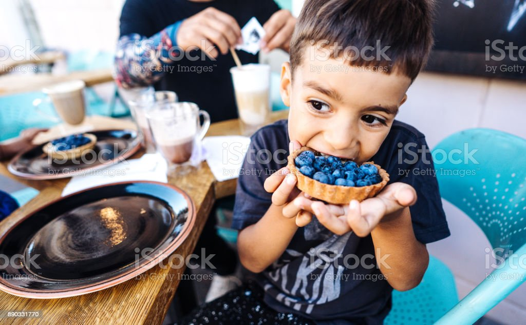 small boy eating dessert with blueberries stock photo