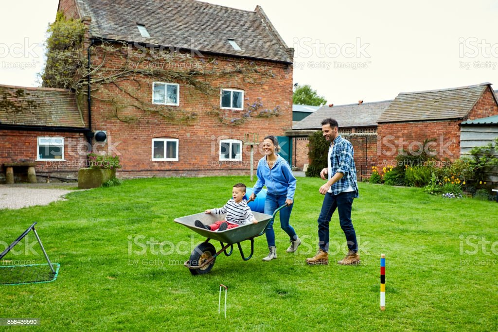 Small boy enjoying in a wheelbarrow with parents in lawn stock photo