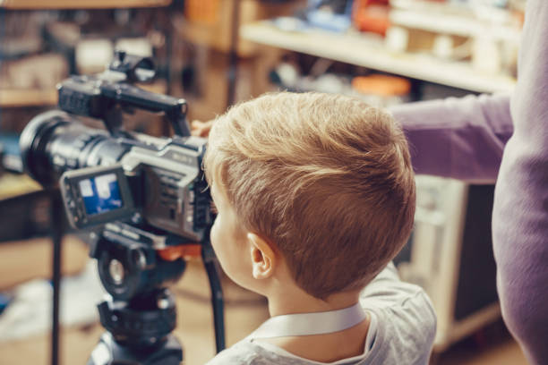 Small boy filming with video camera.