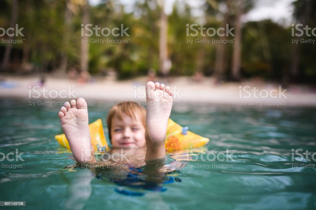 Small boy floating in the sea during summer day. stock photo
