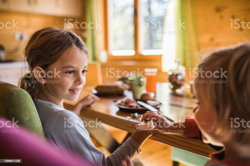 Little boy and his sister having breakfast at home while he is giving...
