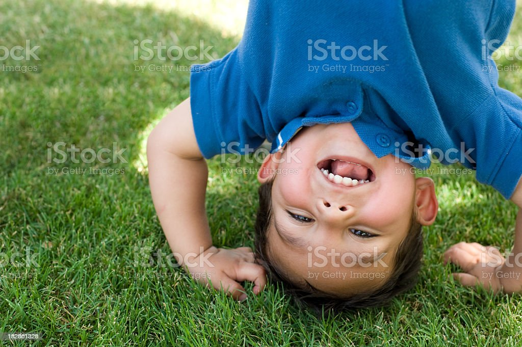 Small boy happily doing a handstand  stock photo