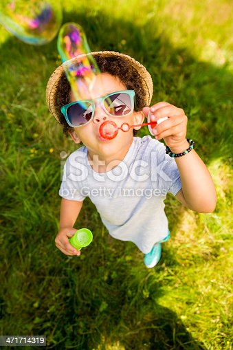 Boy looking up at camera while playing with bubble wand