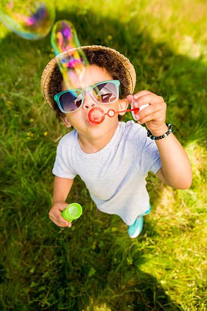 mały chłopiec zabawy dmuchać ma pęcherzyków powietrza - summer background zdjęcia i obrazy z banku zdjęć