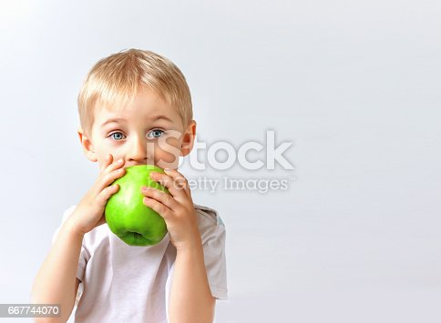 istock small boy holds a big green apple, healthy food and vitamins, smiling, white background, soft focus 667744070