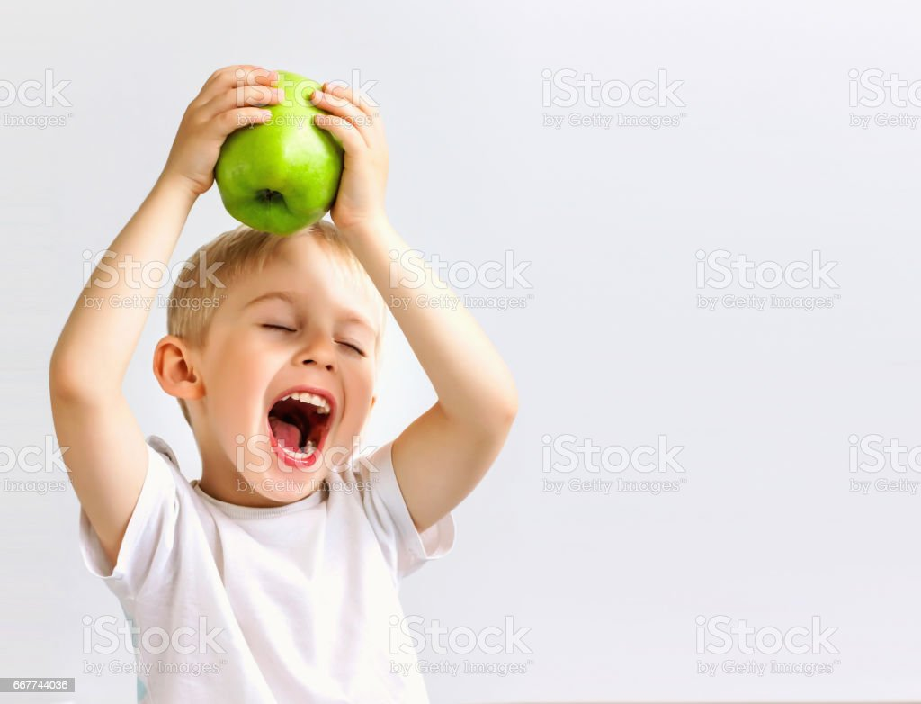 small boy holds a big green apple, stock photo