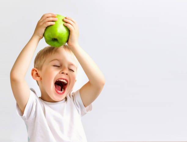 small boy holds a big green apple, - apple fruit stock photos and pictures